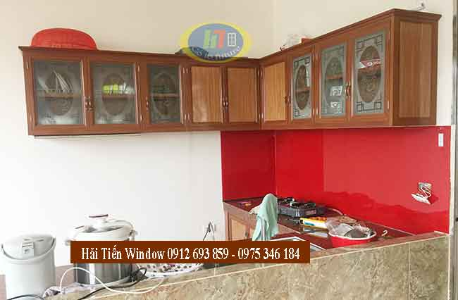 Tủ bếp nhôm kính vân gỗ nhạt và kính ốp bếp màu đỏ sang trọng